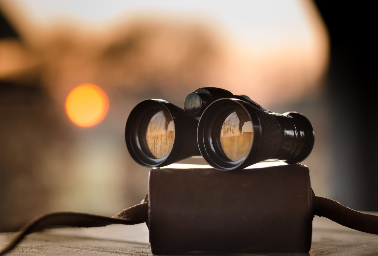 Tri-Source resourcing image of binoculars on a table in front of an out of focus sunset