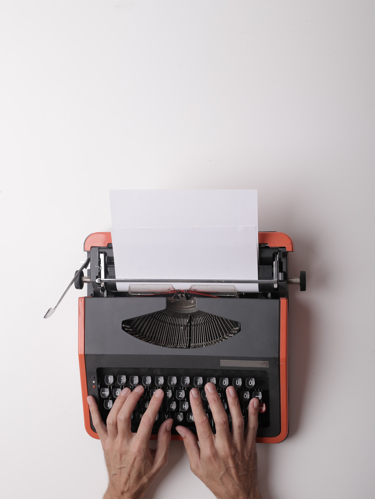 hands drafting ad copy on a bright orange typewriter