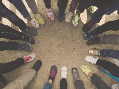 A diverse group of feet placed into a team circle