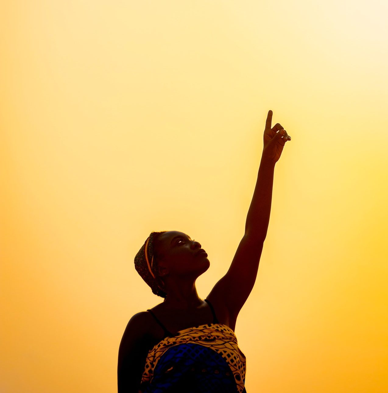 Woman standing against a warm yellow backdrop holding her hand in the air like the IWD #ChooseToChallenge pose